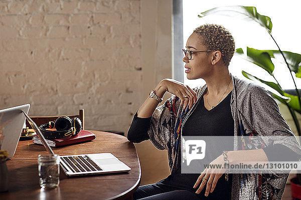 Junge Frau schaut weg  während sie mit Laptops am Tisch sitzt