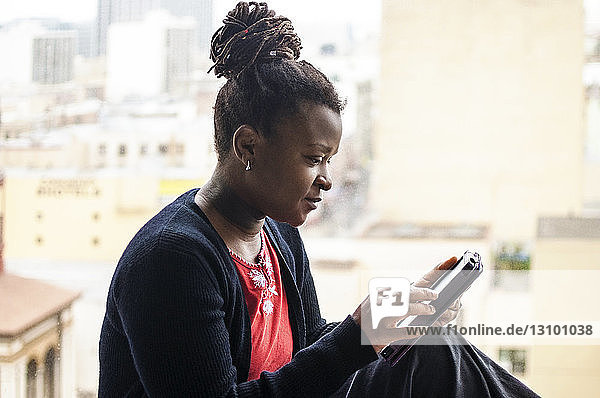 Woman using smart phone while sitting against cityscape