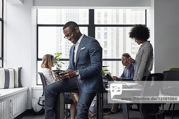Geschäftsmann und Geschäftsfrau benutzen Smartphones  während ihre Kollegen im Büro arbeiten