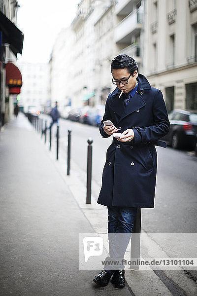 Mann benutzt Smartphone  während er sich am Fußweg auf einen Poller stützt