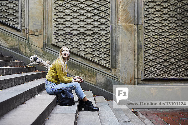 Side view of woman looking away while sitting on steps at park