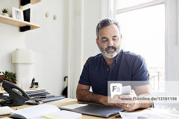 Geschäftsmann nutzt Smartphone  während er am Schreibtisch im Kreativbüro sitzt
