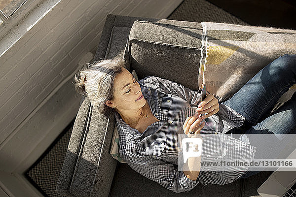 Overhead view of woman using smart phone while lying on sofa at home