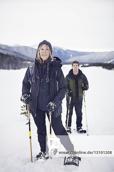 Porträt einer Frau mit ihrem erwachsenen Sohn beim Schneeschuhlaufen