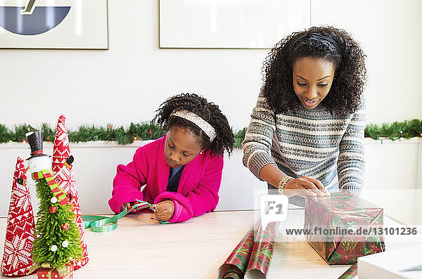 Mother and daughter wrapping Christmas presents at home