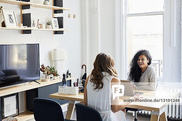 Lächelnde Geschäftsfrau im Gespräch mit einer Kollegin am Schreibtisch im Büro
