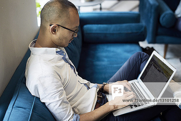 High angle view of businessman using laptop while sitting on blue sofa at creative office