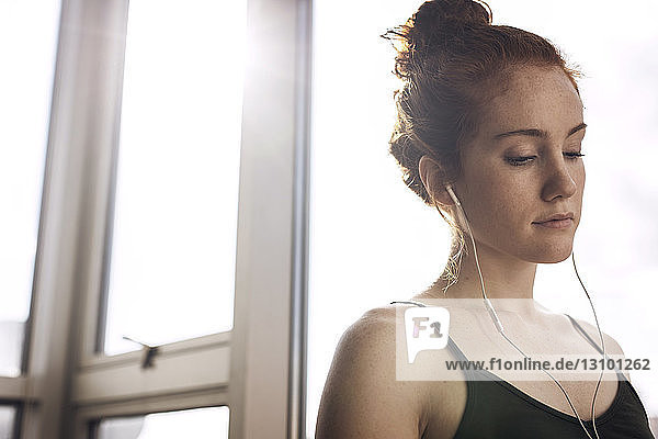 Low angle view of thoughtful woman listening music while standing by window