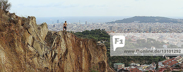 Panoramic view of physically challenged shirtless man standing on cliff against cityscape