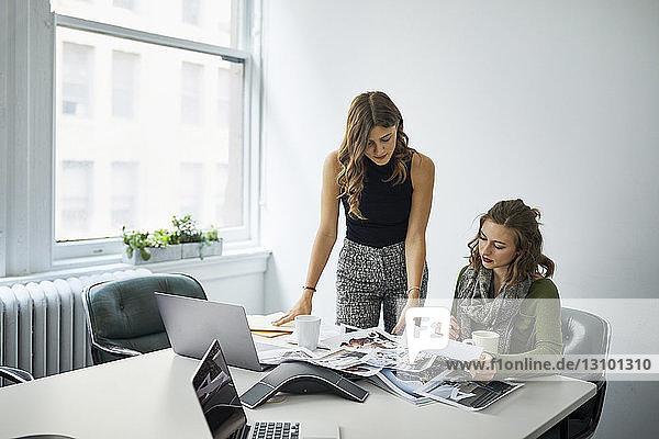 Geschäftsfrauen sehen sich Dokumente an  während sie im Sitzungssaal zusammenarbeiten