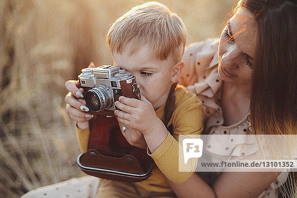 Mother helping son to photograph with vintage camera on field