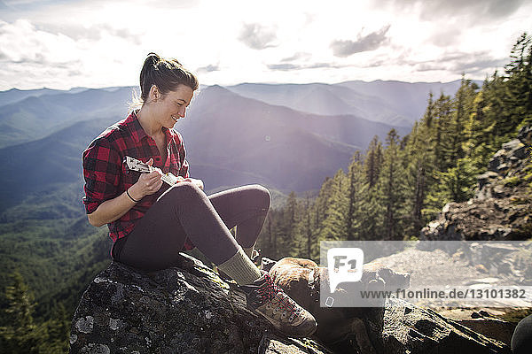 Woman sitting with dog on rock and playing ukelele at mountain cliff