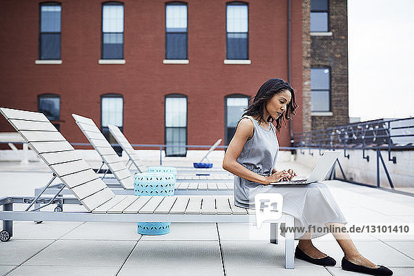 Full length of businesswoman using laptop while sitting on lounge chair at building terrace