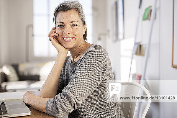 Portrait of confident woman sitting at table in home office