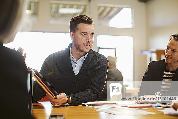 Businessman explaining to colleagues through tablet computer at table in office