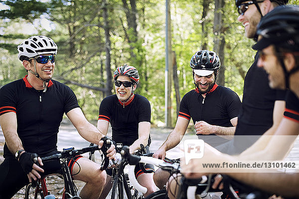 Happy male cyclists relaxing on bicycles