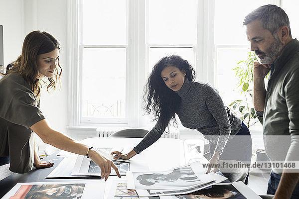 Geschäftsleute diskutieren über Fotoausdrucke im Konferenzraum