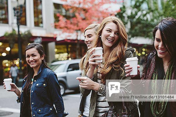Fröhliche Freundinnen trinken Kaffee beim Spaziergang auf der Straße