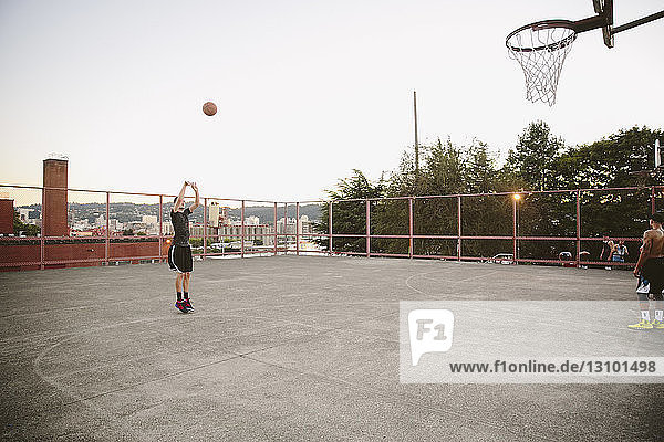 Friends practicing basketball on court against clear sky