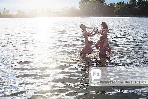 Male friends carrying women on shoulders while enjoying in river