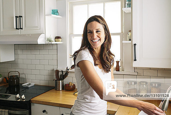 Happy woman looking away while washing dish in kitchen at home