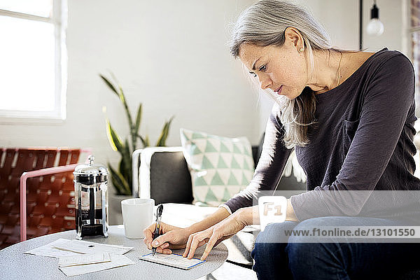 Concentrated woman writing on paper at table in living room