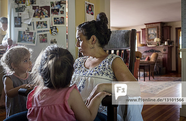 Daughters standing by mother sitting on chair at home