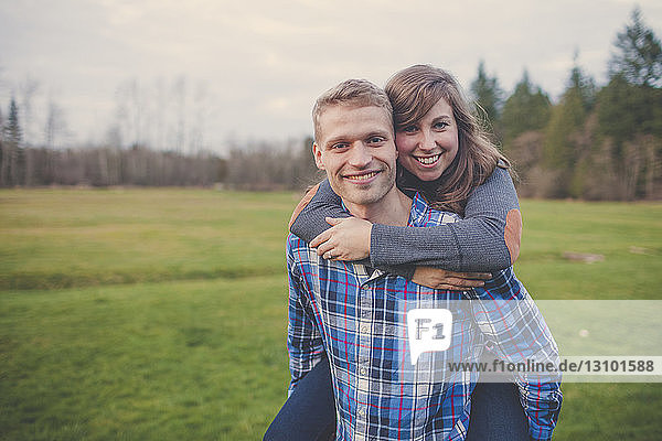 Portrait of husband piggybacking wife while standing on grassy field