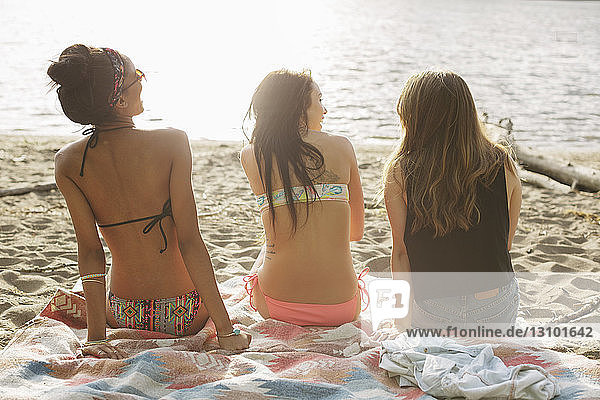 Rear view of female friends sitting on picnic blanket at riverbank