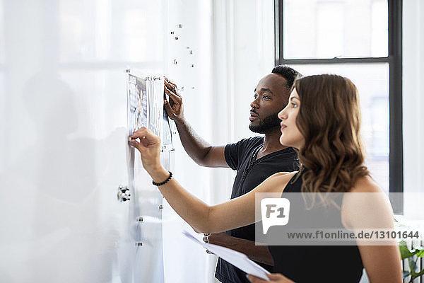 Seriöse Geschäftskollegen betrachten Fotoausdrucke  die am Schwarzen Brett im Büro angebracht sind