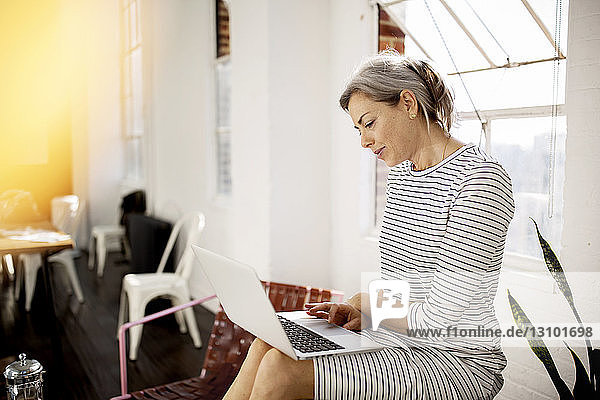 Mature woman using laptop while sitting in living room at home