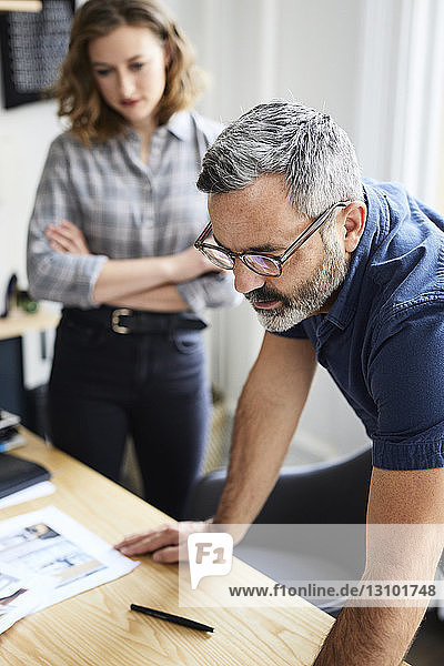 Businessman discussing with female colleague at desk in creative office