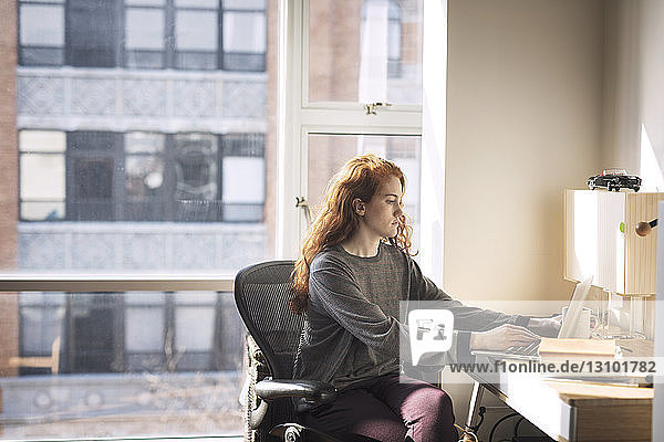 Woman using laptop computer while sitting by window at home
