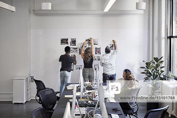 Geschäftsleute befestigen Fotoausdrucke am Schwarzen Brett  während weibliche Kollegen im Büro am Konferenztisch sitzen