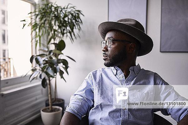 Nachdenklicher Geschäftsmann schaut weg,  während er in einem kreativen Büro auf einem Stuhl sitzt