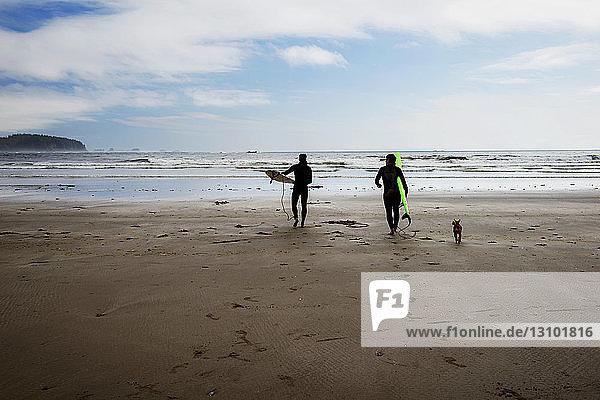 Surfers walking on beach against sky