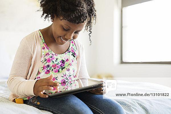 Lächelndes Mädchen benutzt Tablet-Computer im Schlafzimmer