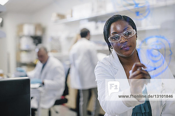 Female doctor writing on glass window with coworkers in background at medical room