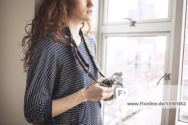 Midsection of woman with camera standing by window at home