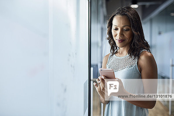 Smiling businesswoman using mobile phone while standing by glass wall at creative office