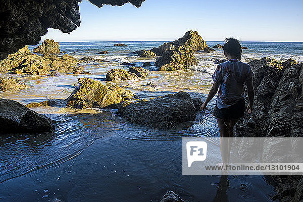 Rückansicht einer am Ufer stehenden Frau durch eine Höhle gesehen