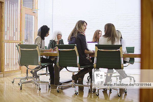 Female colleagues discussing in meeting at board room