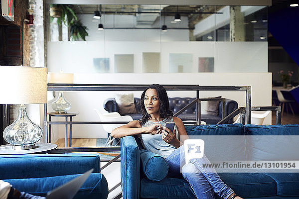 Thoughtful businesswoman using mobile phone while sitting on sofa at creative office