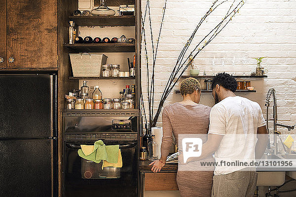 Rear view of man standing arm around woman at kitchen counter