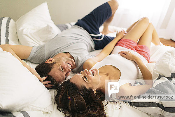 High angle view of cheerful couple in bed at home