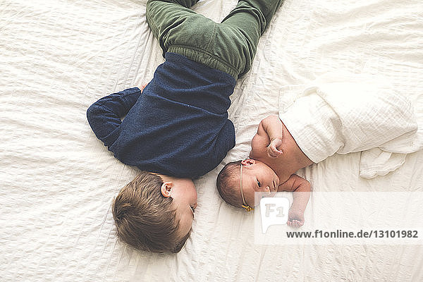 High angle view of siblings lying on bed at home High angle view of siblings lying on bed at home