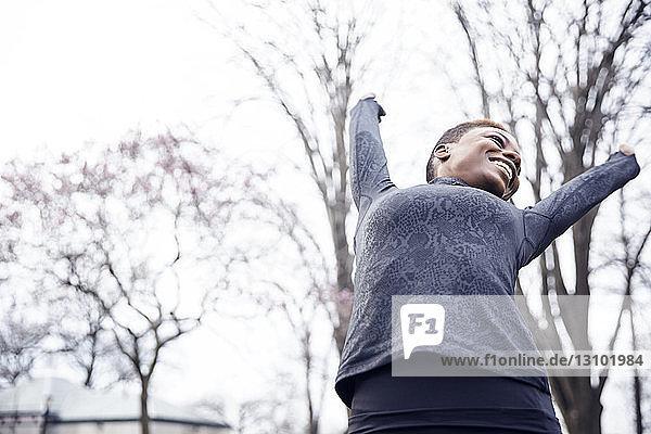 Niedrigwinkelansicht einer glücklichen Athletin  die im Park die Arme ausstreckt
