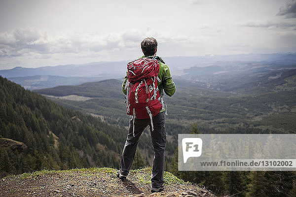 Rear view of hiker with backpack standing on mountain against sky
