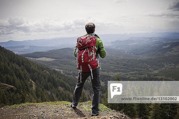 Rückansicht eines auf dem Berg stehenden Wanderers mit Rucksack gegen den Himmel