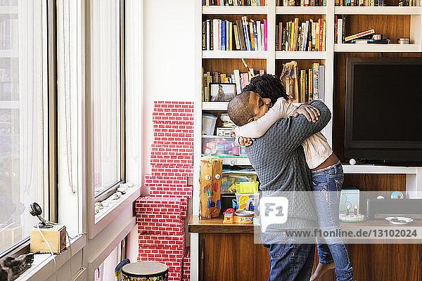 Seitenansicht eines Mannes  der seine Tochter umarmt  während er zu Hause steht